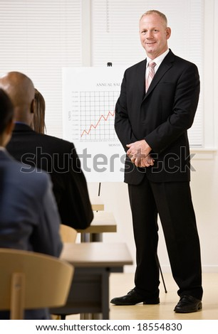 Confident businessman explaining financial analysis chart to co-workers - stock photo