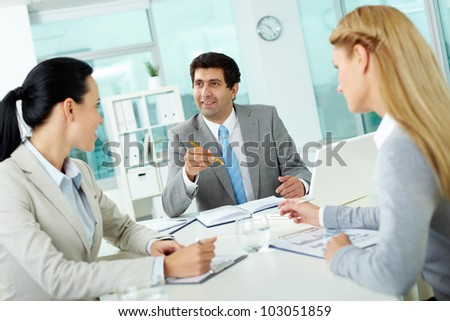 Confident businessman explaining his ideas to employees at meeting - stock photo