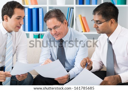 Confident businessman explaining his plan of work to colleagues at meeting - stock photo