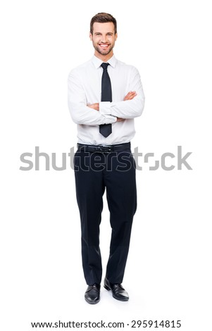 Confident businessman. Full length of smiling young businessman keeping arms crossed and looking at camera while standing against white background - stock photo