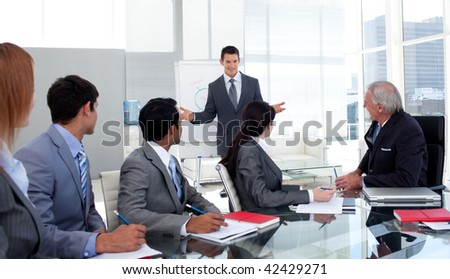 Confident businessman giving a presentation to his team in the office - stock photo