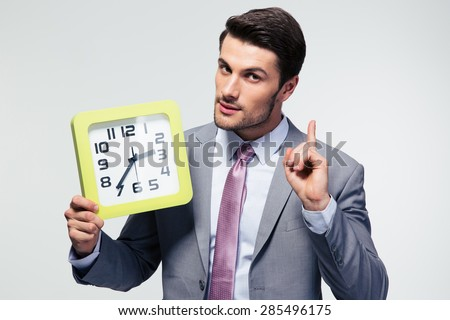 Confident businessman holding clock over gray background and looking at camera - stock photo