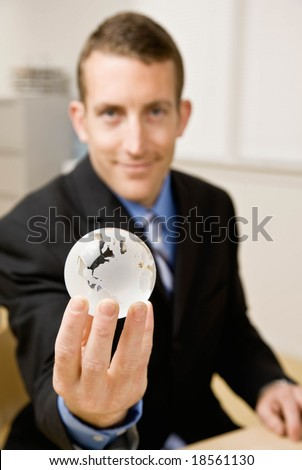 Confident businessman holding glass globe
