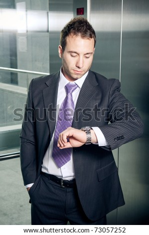 Confident businessman in elevator looking at his watch - stock photo