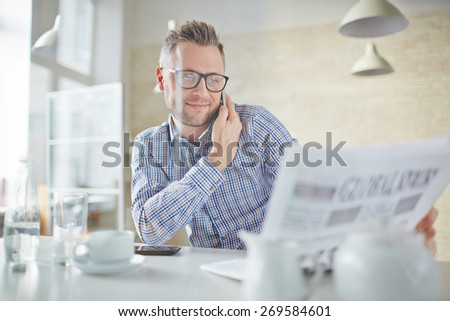 Confident businessman in eyeglasses talking on cellphone while reading newspaper - stock photo