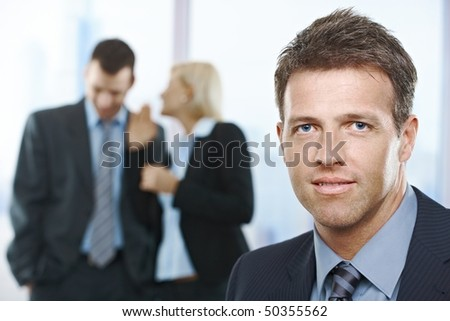 Confident businessman in focus, with standing colleagues talking in the background.