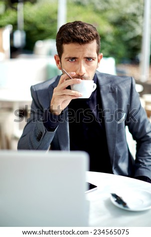 Confident businessman in suit drinking coffee focused in something, wealthy successful man holding cup of coffee sitting in beautiful modern cafe, work break of attractive businessman drinking coffee - stock photo
