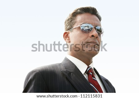Confident businessman in sunglasses - stock photo