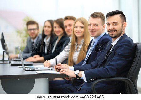 Confident businessman looking at camera among colleagues - stock photo