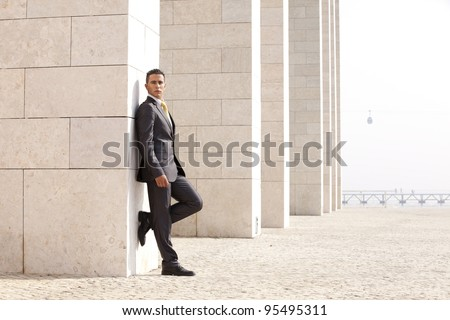 confident businessman next to some wall looking down