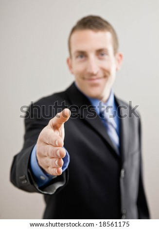 Confident businessman offering hand for handshake - stock photo