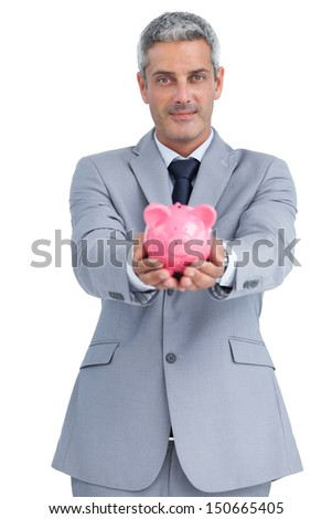 Confident businessman on white background holding piggy bank in both hands - stock photo
