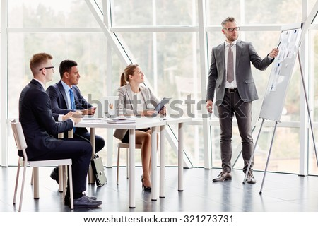 Confident businessman pointing at document on board while explaining his idea to colleagues in office - stock photo