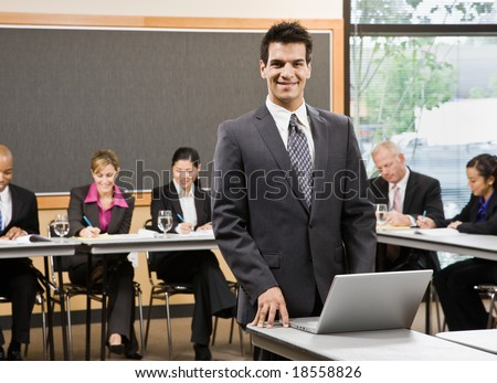 Confident businessman preparing for presentation on laptop in conference room - stock photo