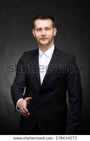 confident businessman reaching out hand to close deal against a dark background - stock photo