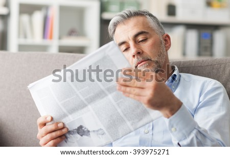 Confident businessman reading a newspaper at home, he is sitting on the couch and relaxing - stock photo
