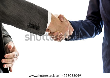 Confident businessman shaking hands with his  female business partner to conclude a deal, agreement, partnership or in congratulations over white background. - stock photo