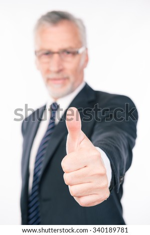Confident businessman showing thumb up - stock photo