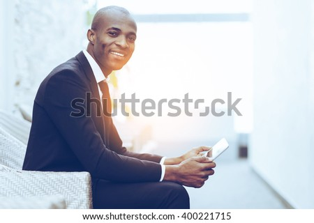 Confident businessman. Side view of cheerful young African businessman working on digital tablet and smiling at camera - stock photo