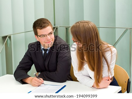 Confident businessman signing the contract in front of his partner - stock photo