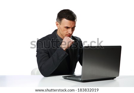 Confident businessman sitting at the table and looking on laptop isolated on a white background