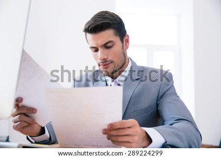 Confident businessman sitting at the table in office and reading documents - stock photo