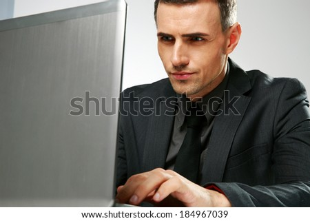 Confident businessman sitting at the table with laptop - stock photo