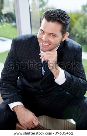 Confident businessman sitting in office by window smiling at camera