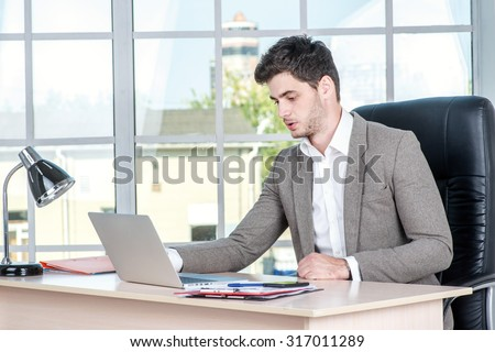Confident businessman sitting in the office and working on laptop. Businessman making successful business.