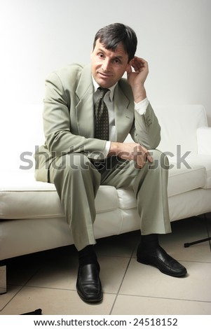 Confident businessman sitting on a white leather sofa