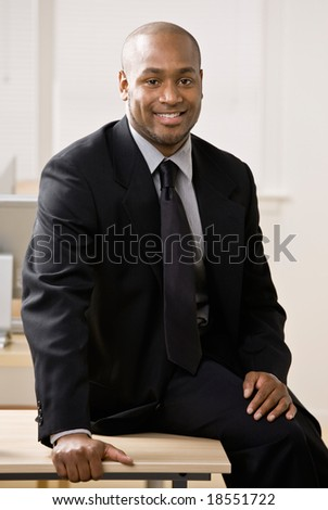 Confident businessman sitting on desk
