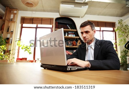 Confident businessman sitting with laptop at office - stock photo