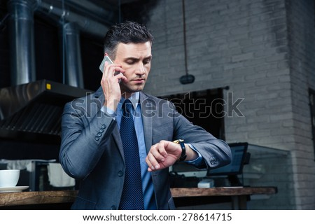 Confident businessman speaking on the phone and looking on the wristwatch in cafe - stock photo