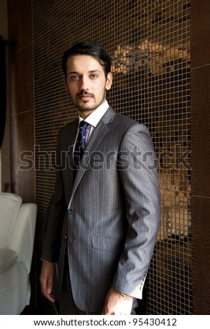 confident businessman standing against tiled wall - stock photo