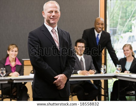Confident businessman standing in front of co-workers in conference room - stock photo
