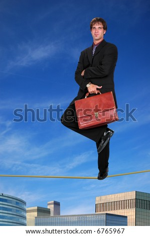 Confident businessman standing on tightrope with buildings in the background.