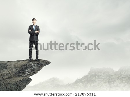 Confident businessman standing on top of rock - stock photo