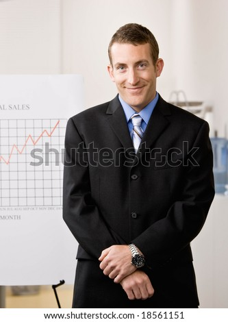 Confident businessman standing with financial analysis chart - stock photo