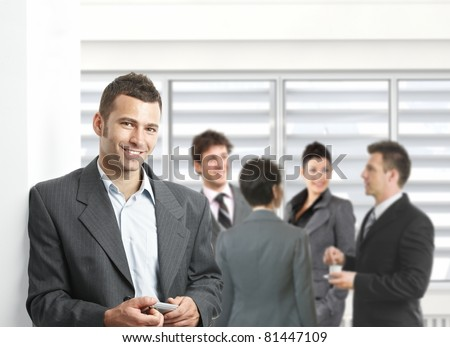 Confident businessman standing with mobile phone in hand in meeting room, colleagues talking. - stock photo