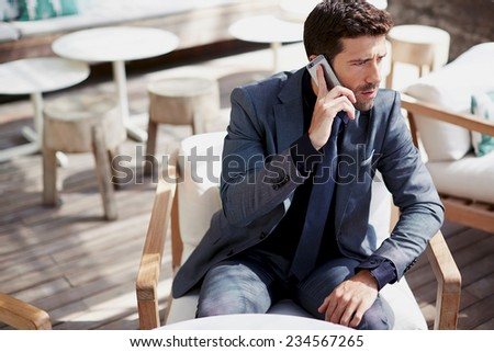 Confident businessman talking on mobile phone sitting in cafe, handsome caucasian business man in suit using mobile phone focused in the work, handsome stylish man talking on smart phone looking away - stock photo