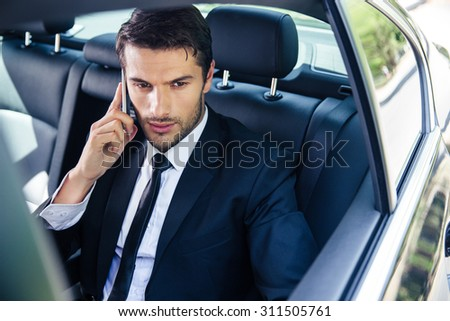 Confident businessman talking on the phone in car - stock photo