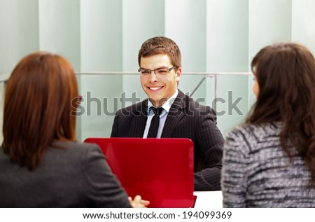 Confident businessman talking with his clients in the office - stock photo