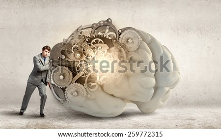 Confident businessman trying to pull huge human brain - stock photo