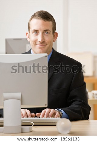 Confident businessman typing on computer at desk - stock photo