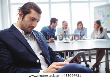 Confident businessman using digital tablet against colleagues in meeting room at office - stock photo