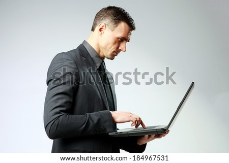 Confident businessman using laptop on gray background - stock photo