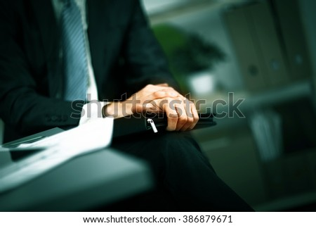 confident businessman with a folder in his hands in the office - stock photo