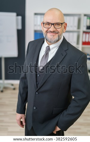 Confident businessman with a friendly smile standing with his and in his pocket in the office smiling at the camera, conceptual of leadership and management - stock photo