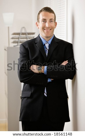 Confident businessman with arms crossed leaning on wall - stock photo