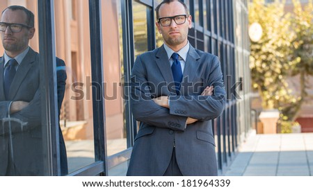 Confident businessman with arms crossed next to his office building